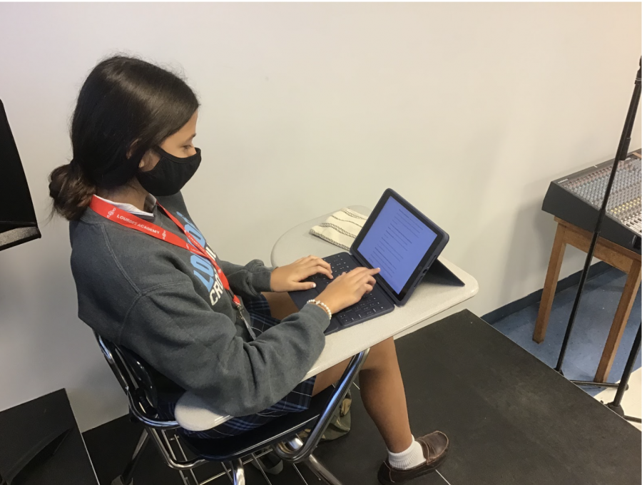 """Junior Mia Puente takes notes on her iPad in her anatomy class on Wednesday. This was Mia's first day back on campus with the new hybrid schedule after leaving campus March 13. """"It was an amazing day to finally be back and see most of my friends along with my teachers,"""" said Puente."""